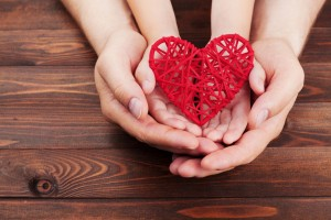 62038274 - adult and child holding red heart in hands over a wooden table. family relationships, health care, pediatric cardiology concept.